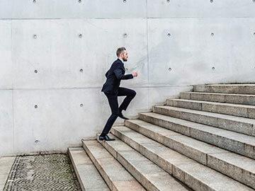 Business Mann der die Treppe hoch läuft - Externer Vertrieb